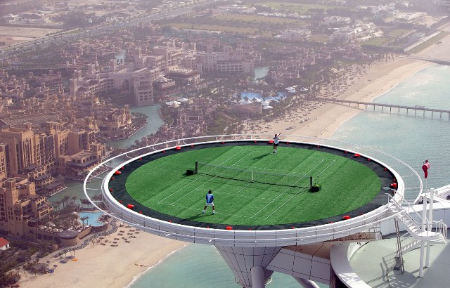 DUBAI,- FEBRUARY 22: In preparation for the Dubai Duty Free Men's Open, tennis legend Andre Agassi of the USA and the World's No. 1 Roger Federer of Switzerland, couldn't resist the temptation to have a friendly 'hit' on the world's most unique tennis court, the Helipad of the Burj Al Arab, the world's most luxurious hotel. Standing 321 metres high on a man made island, the majestic Burj Al Arab is without doubt the most recognizable hotel in the world. The hotel's helipad, which is situated 211 metres high covers a surface area of 415 square metres. Roger Federer is the reigning champion of the Dubai Duty Free Men's Open and is making his third appearance in the tournament. For Agassi this is his first time to appear in the ATP tournament where he has already progressed to the second round having beaten Radek Stepanek of the Czech Republic.  The pictures were taken on February 22, 2005, in Dubai, United Arab Emirates.  (Photo by David Cannon/Getty Images)